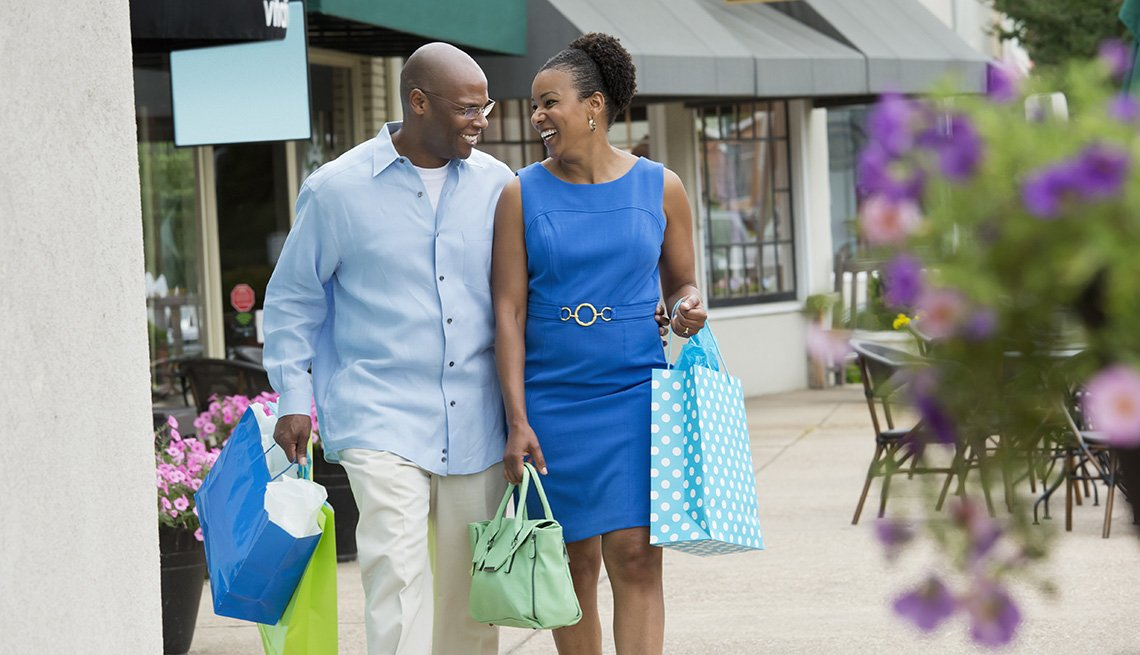 An African American Couple On Sidewalk With Stores In Background Carrying Shopping Bags, In Livable Communities Slideshow