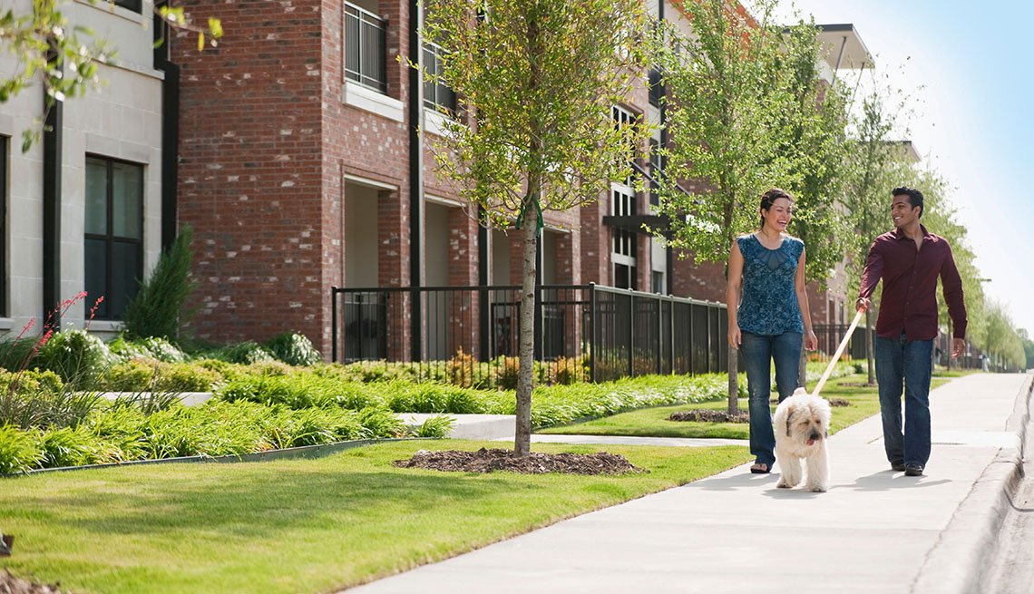 A Young Couple Walks Their Dog Past Apartment Complex, In Livable Communities Slideshow