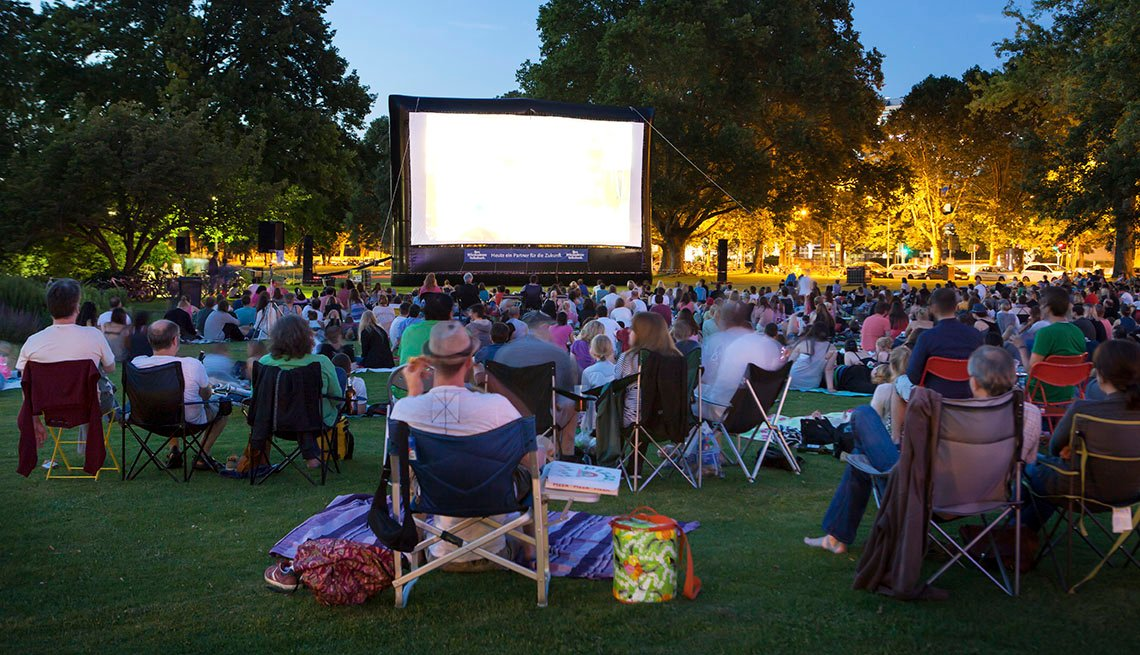 A Crowd Of People Sit On The Grass In Park To Watch A Free Movie, Movies In The Park, In Livable Communities Slideshow