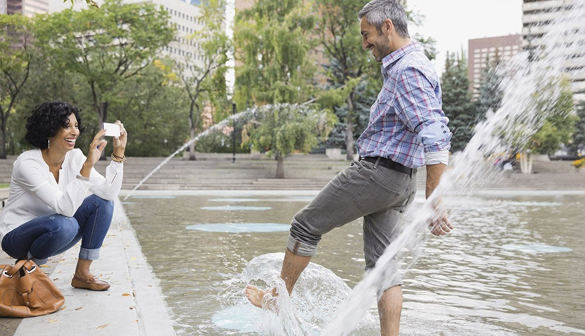 Woman Takes Man's Picture While He Stands In Public Fountain Splashing Water, Urban Setting, Buildings In Background, Water, In Livable Communities Slideshow