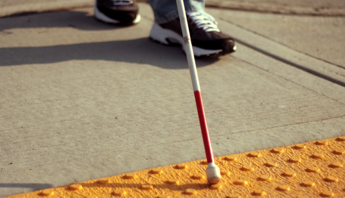 Close-up image of a person's feet and walking cane while approaching a the end of a sidewalk