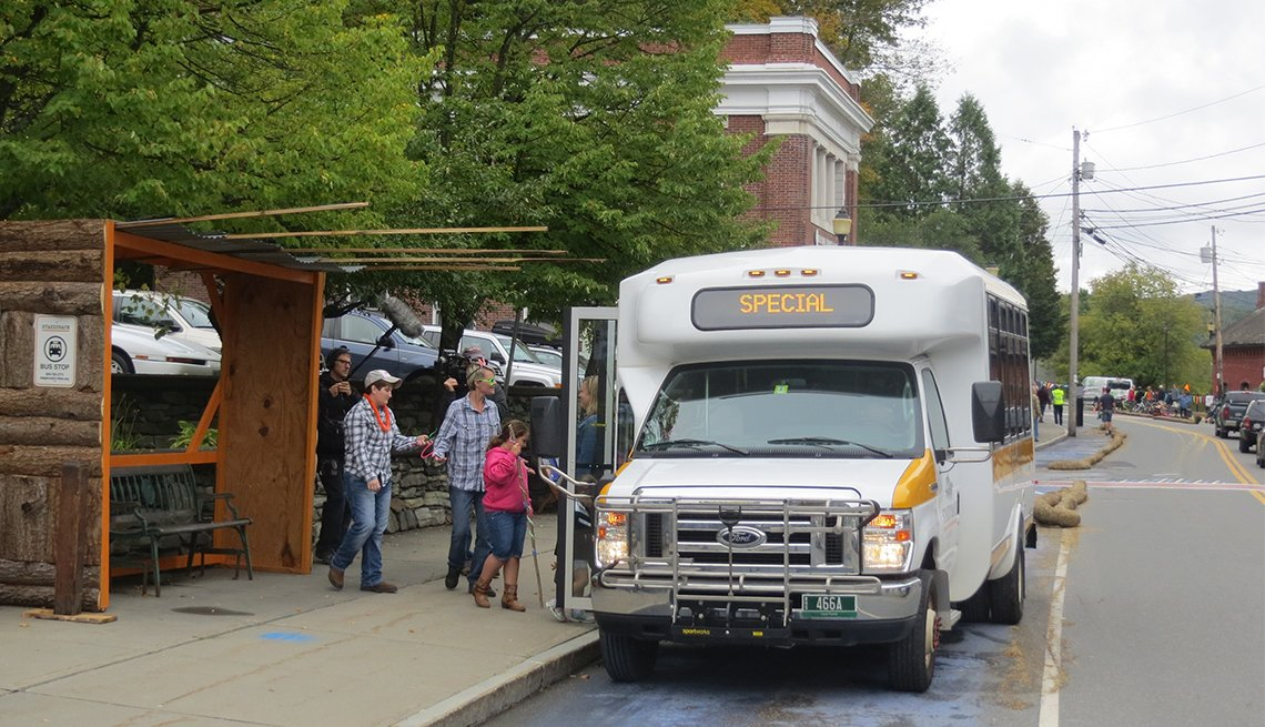 A temporary bus shelter made of logs and wood provides shelter for people as they wait for the shuttle bus.