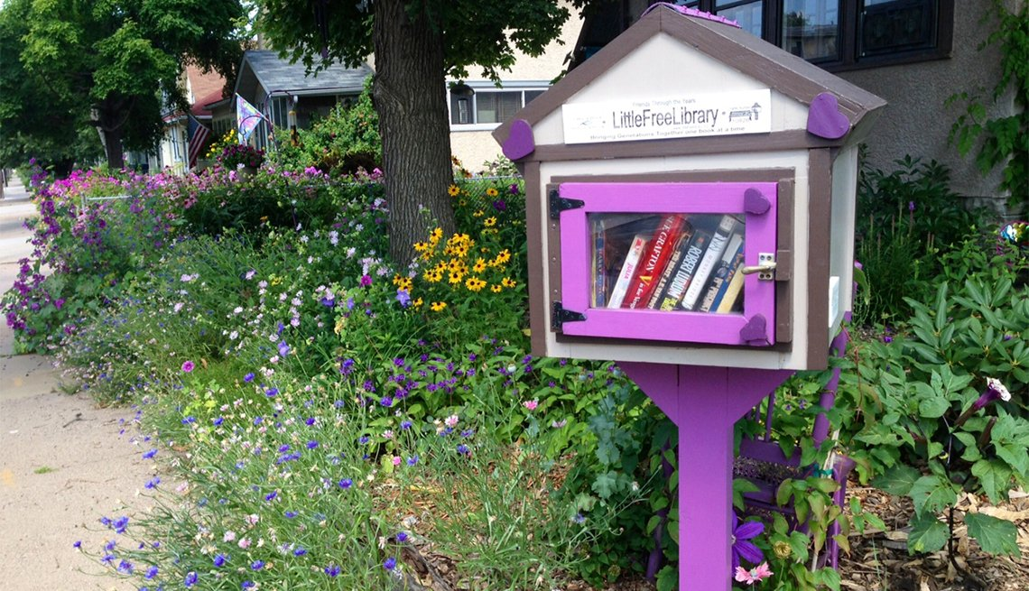 A purple Little Free Library is surrounded by wildflowers in Minneapolis.