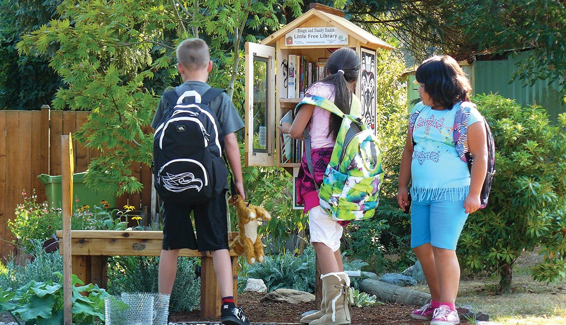 Three children visit a Little Library in Mountainlake Terrace, Washington