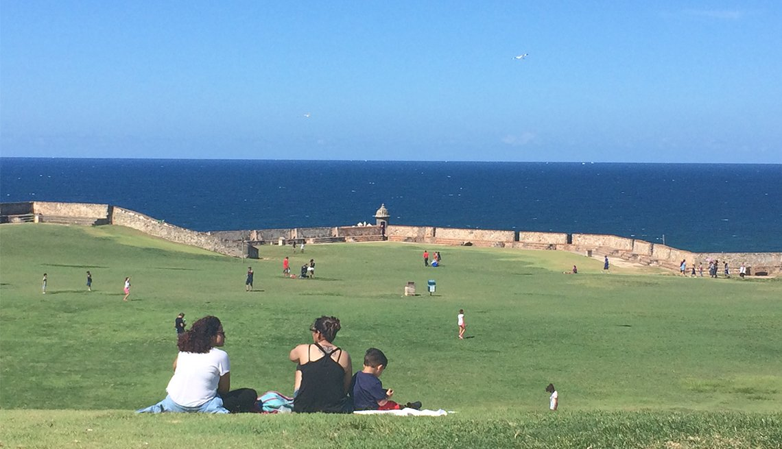 A family has a picnic on a green lawn with an ocean view in Puerto Rico