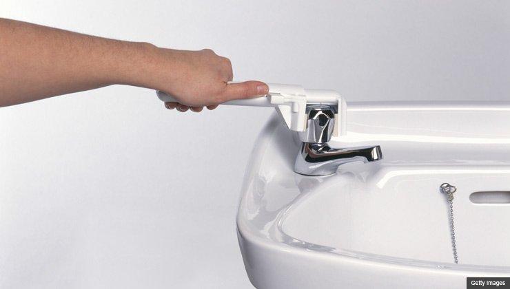 Hand using plastic lever on bathroom basin tap, close-up
