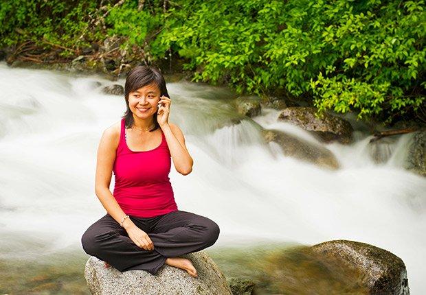 Be calm. Woman on phone doing yoga