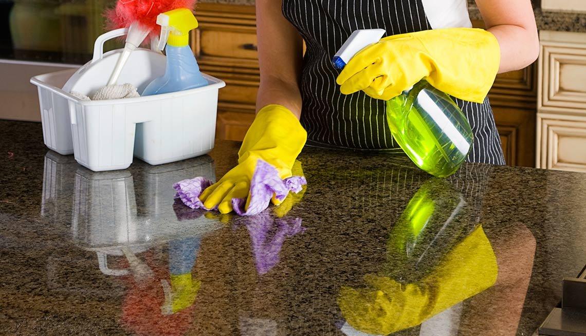Mujer con guantes limpiando una superficie de granito - Evita reparaciones costosas en el hogar