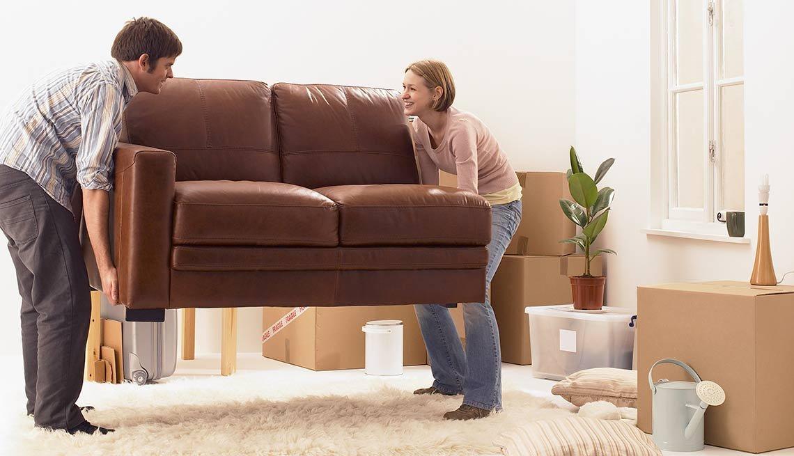 Hombre y mujer moviendo un sofá sobre un tapete - Evita reparaciones costosas en el hogar