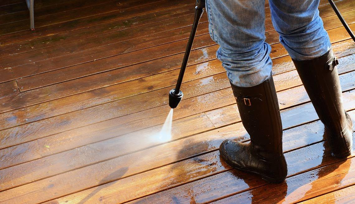 Hombre lavando piso de madera con una manguera a presión - Evita reparaciones costosas en el hogar