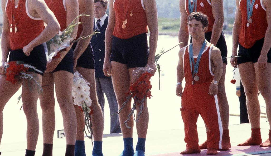 Hombre pequeño con traje de atletismo al lado de las piernas de hombres altos - Becas universitarias inusuales
