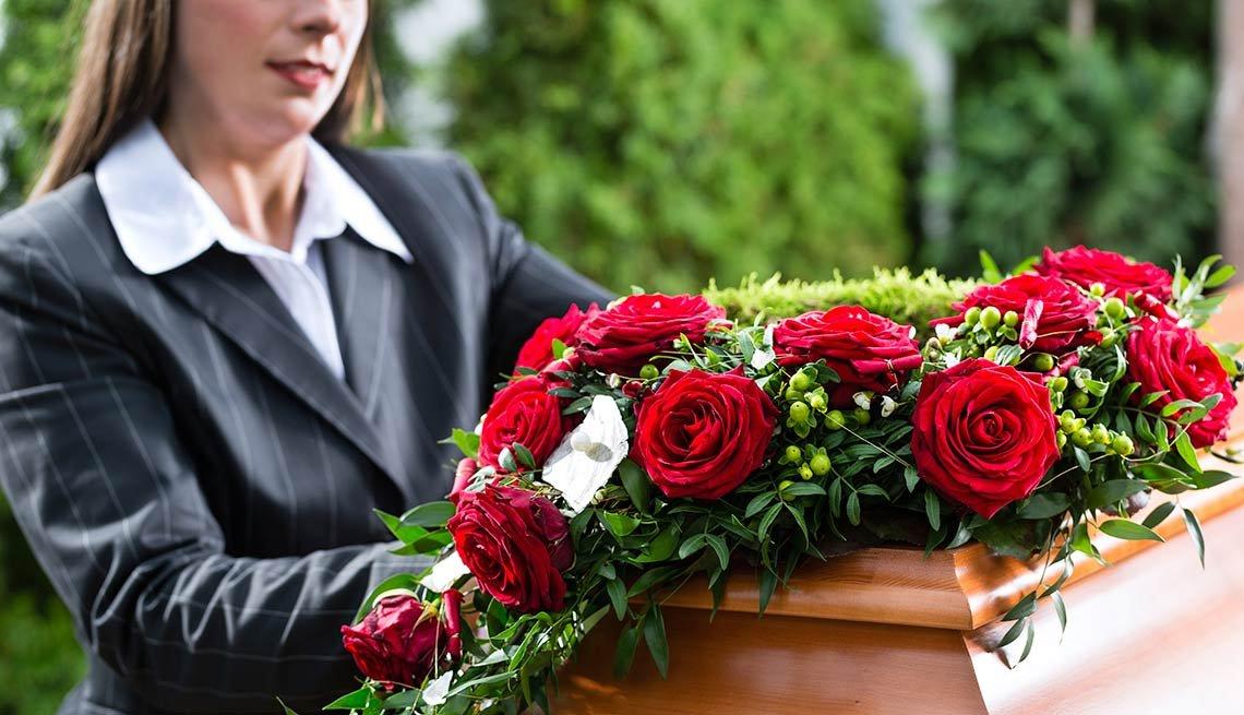 Mujer frente a un ataud con ramo de rosas encima   - Becas universitarias inusuales