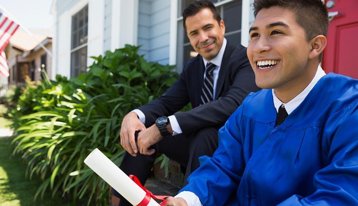 Hombre vestido de traje y corbata al lado de un adolescente con toga y diploma de graduación - Becas universitarias inusuales