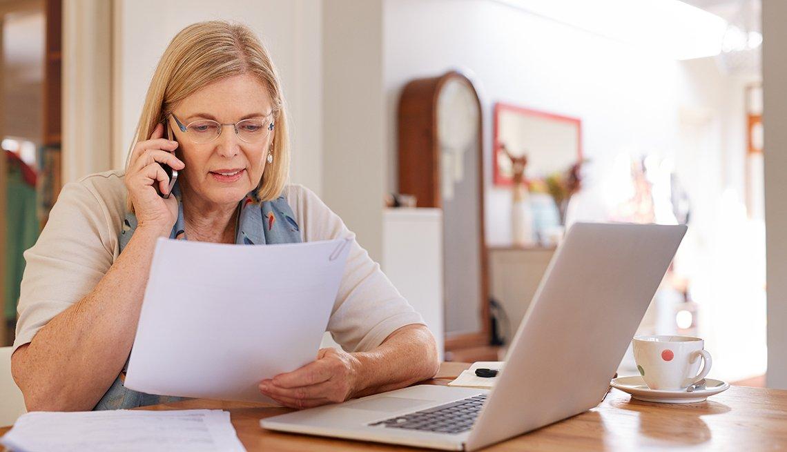 Mujer viendo papeles frente a una computadora personal mientras ve cómo reducir el costo de sus facturas