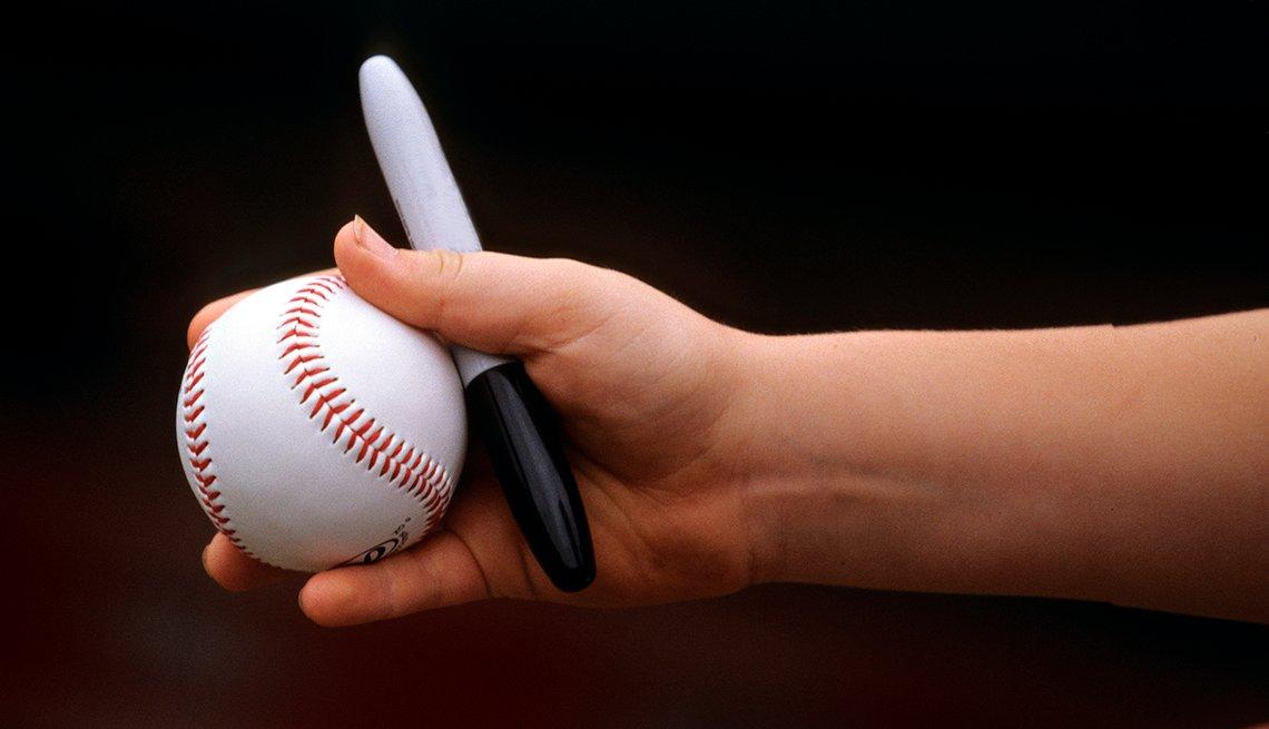 Mano sosteniendo una pelota de béisbol y un marcador, y formas de gastar $100 dólares