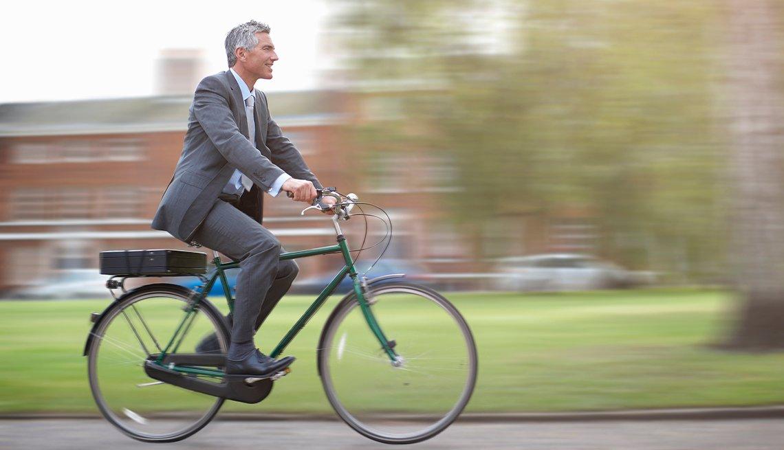 Hombre con traje y corbata en una bicicleta - Cómo ahorrar 10 mil dólares al año