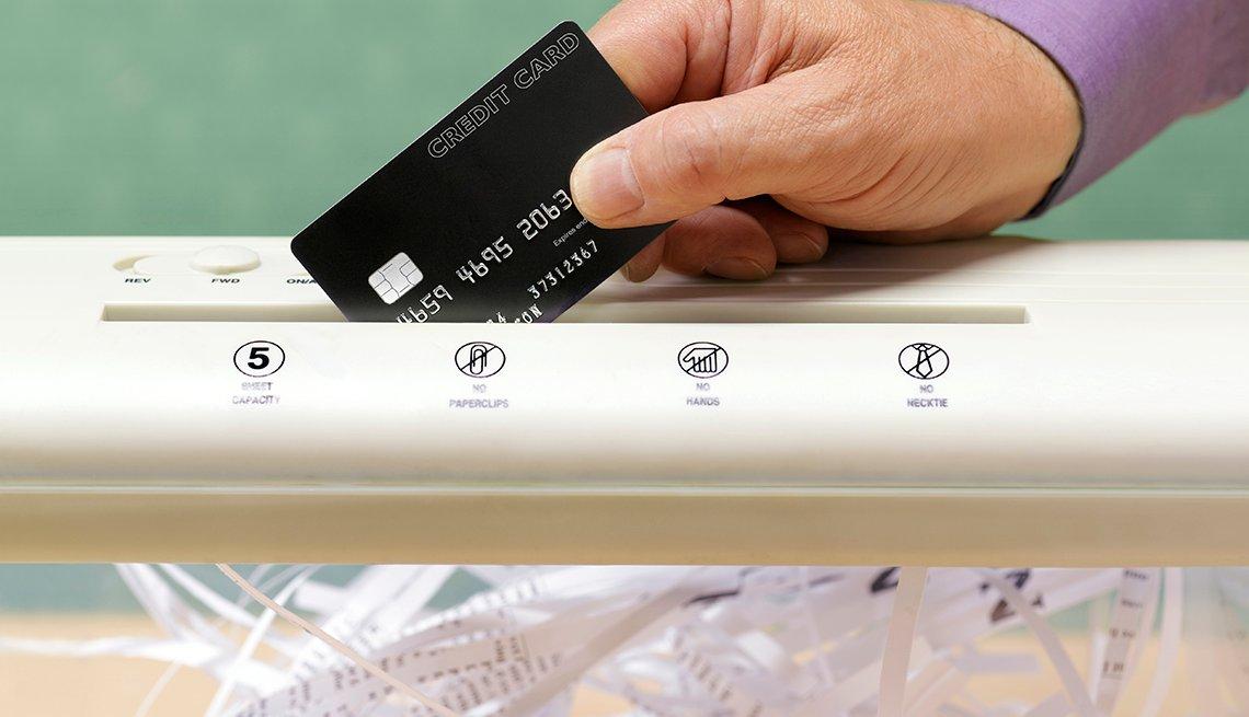 Mano sosteniendo una tarjeta de crédito en una máquina trituradora de papel - Errores comunes con las tarjetas de crédito