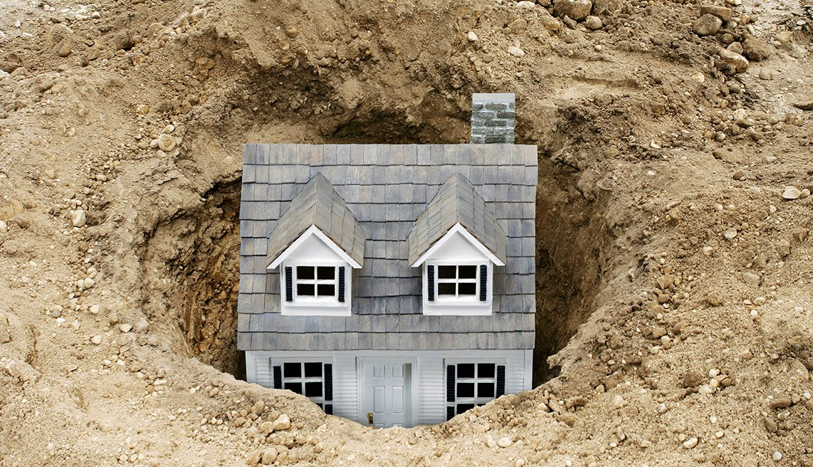 Maqueta de una casa enterrada en un hueco de tierra - Errores comunes con las tarjetas de crédito