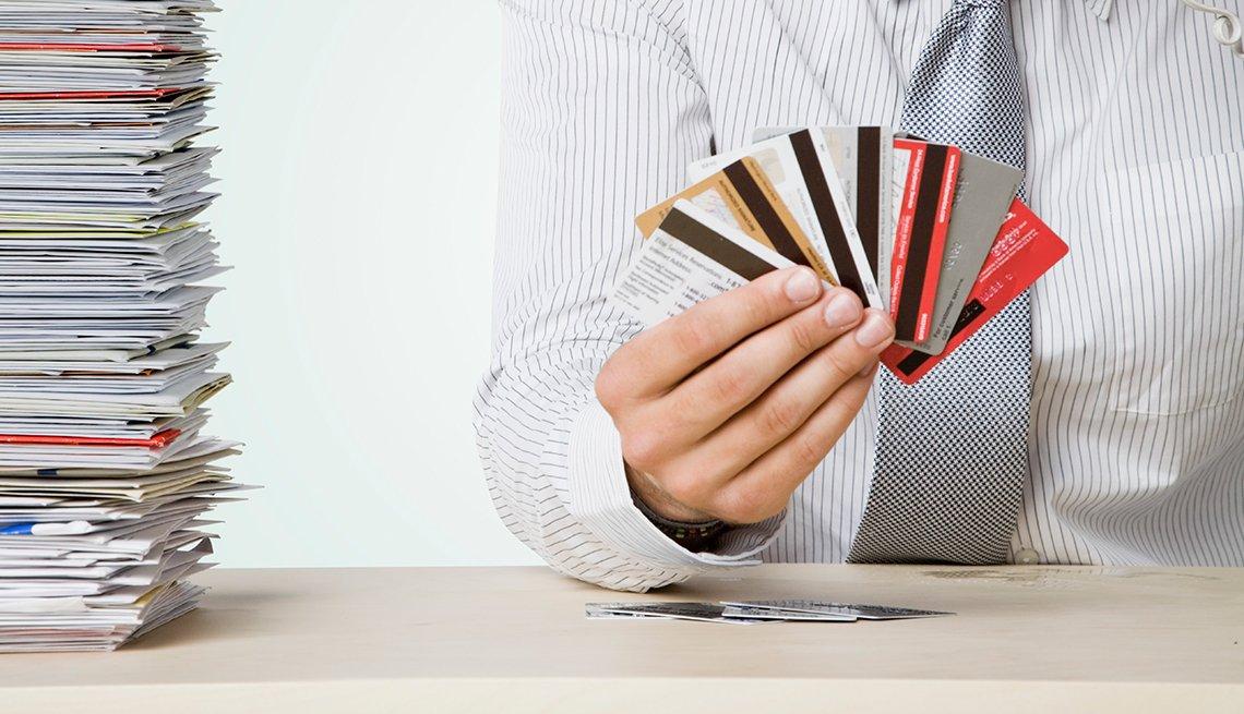Hombre sosteniendo tarjetas de crédito en la mano - Errores frecuentes al comprar un negocio