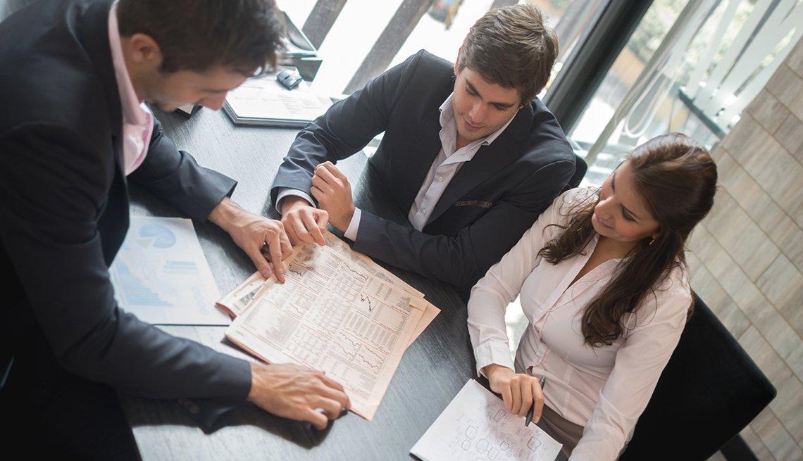 Hombre revisando un contrato con una pareja - Errores frecuentes al comprar un negocio