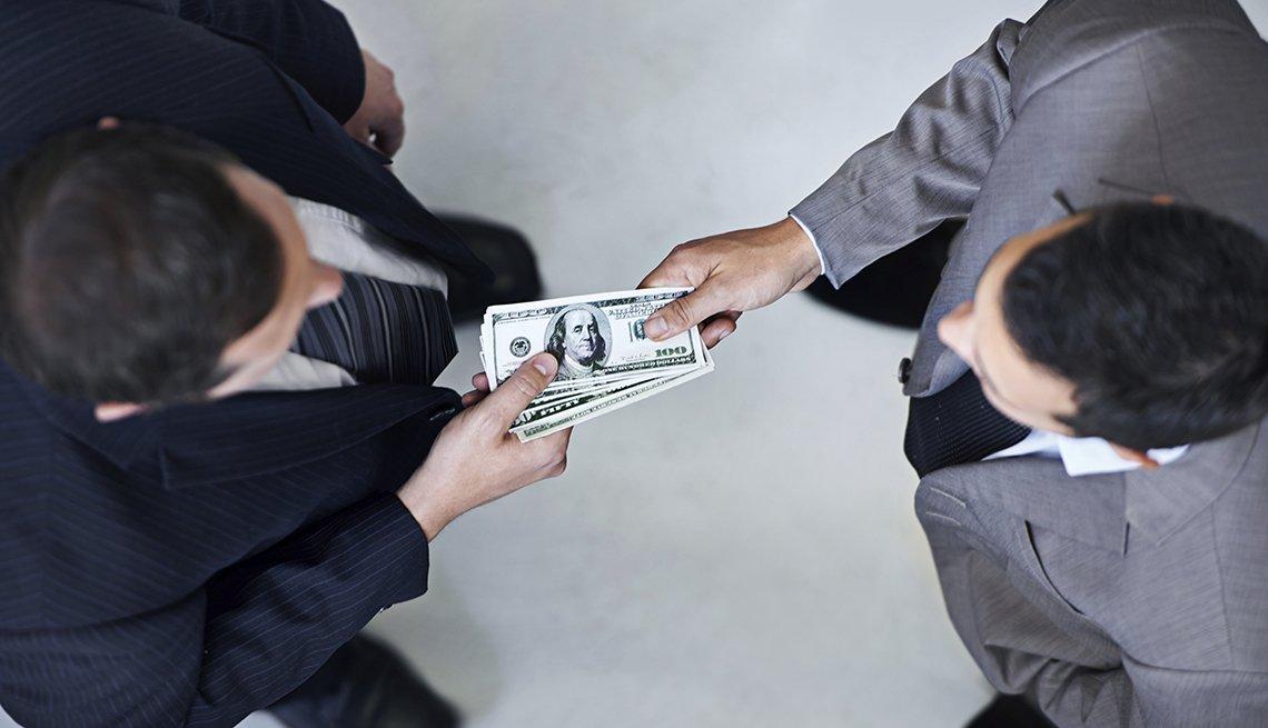 Un hombre dándole a otro dólares - Errores frecuentes al comprar un negocio