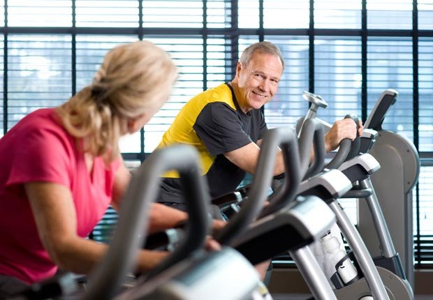Man and woman riding bikes in health club (Juice Images/Alamy)