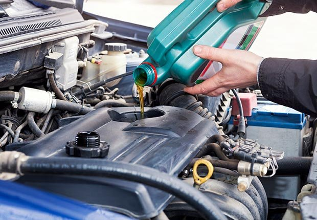 Adding oil to car engine (Istockphoto)