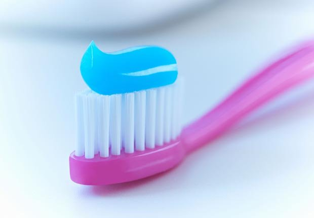 Purple toothbrush with toothpaste. (Adrian Gaultier/Alamy)
