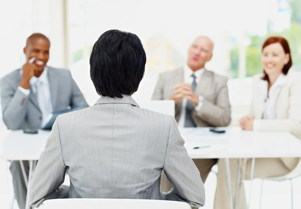 Mujer entrevistada por un grupo de hombres de negocios. Tener mal crédito puede afectar sus perspectivas de empleo.