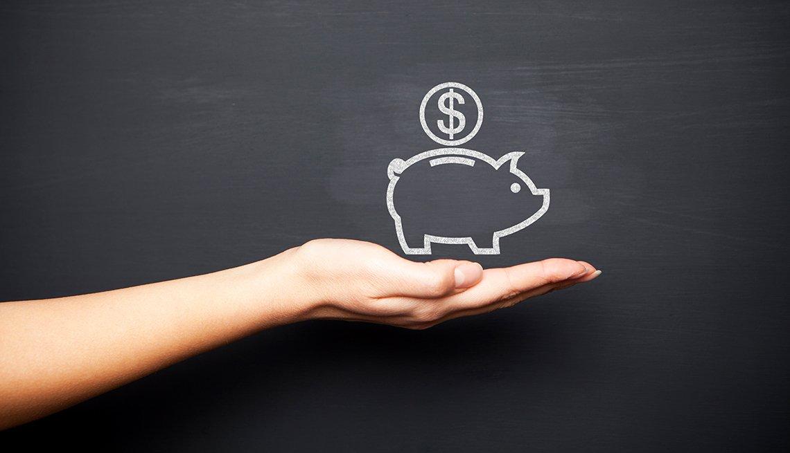 Una mano sosteniendo una ilustración de una alcancía en forma de cerdo y con el signo de dólar dentro de un círculo
