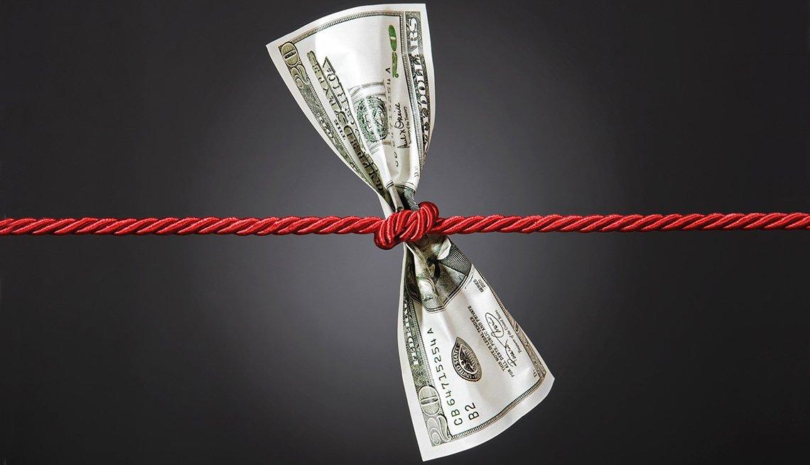 Billete de cien dólares anudado a un lazo rojo