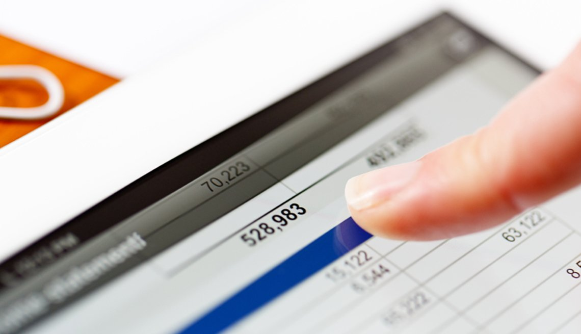 Formas de protegerte contra el robo de identidad - Un dedo sobre la pantalla de un computador viendo el estado de una cuenta de banco