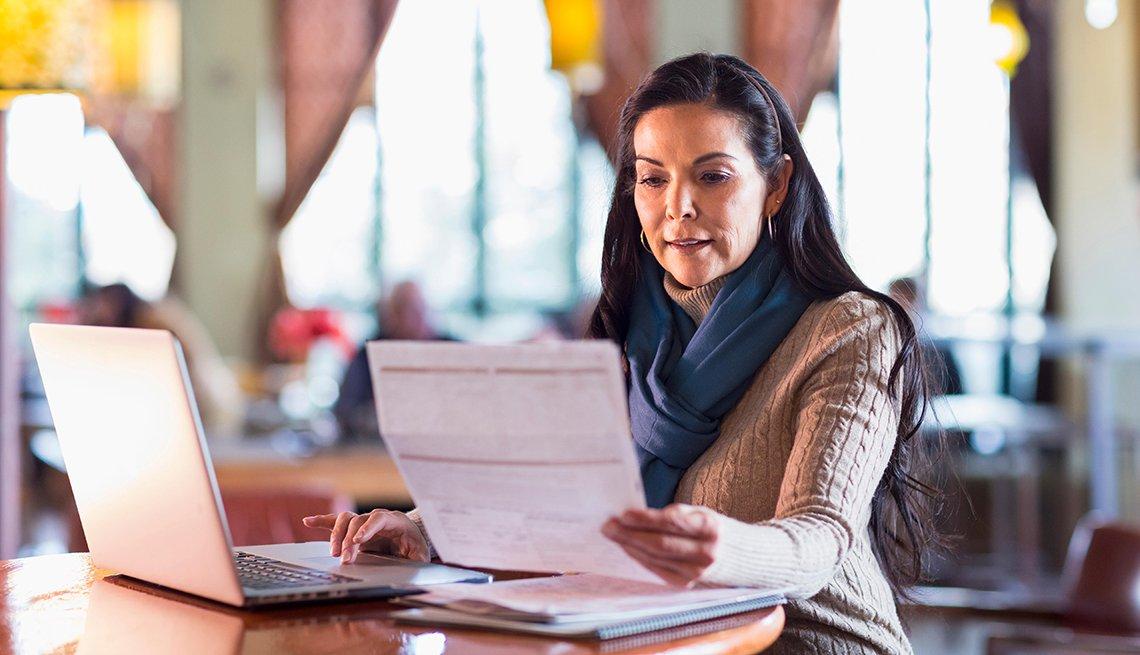 Mujer en un cafe revisando cuentas en un computador, pero si usas una red wifi pública hay cosas que no deberías hacer