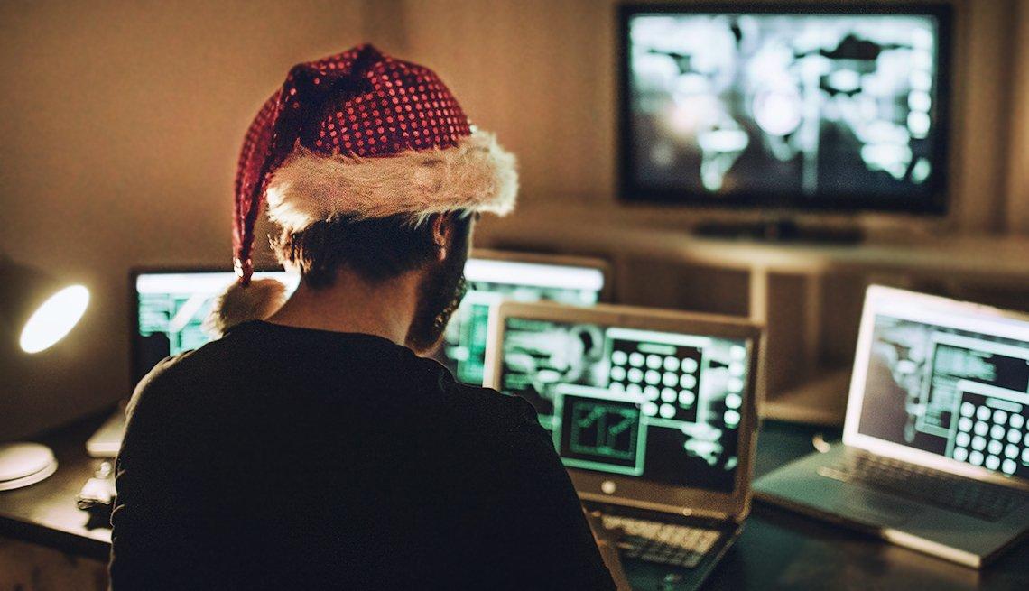Hombre con un gorro de navidad frente a varias computadoras y cuidado con las fiestas de fin de año.