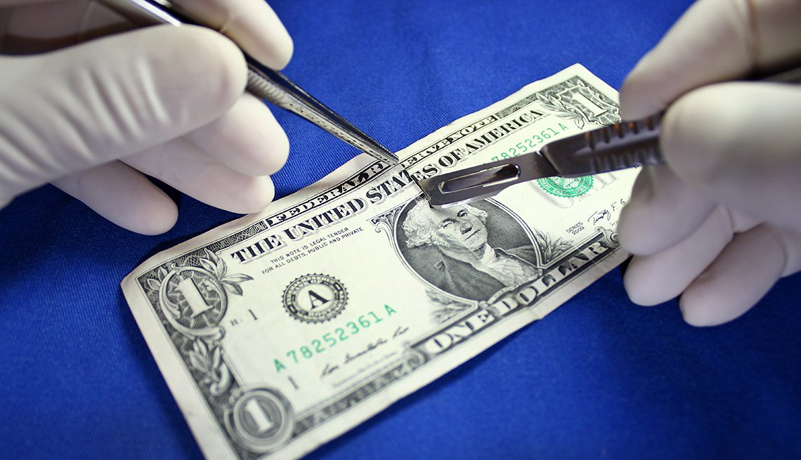 Surgical hands cutting a dollar bill
