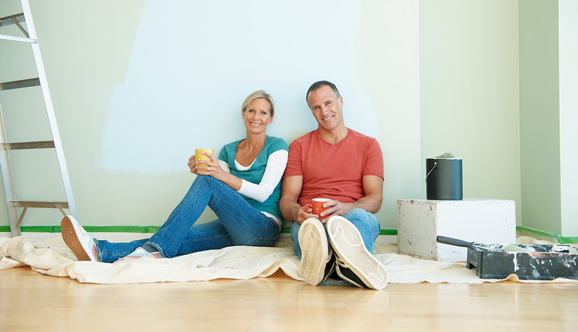 Couple resting after painting a wall
