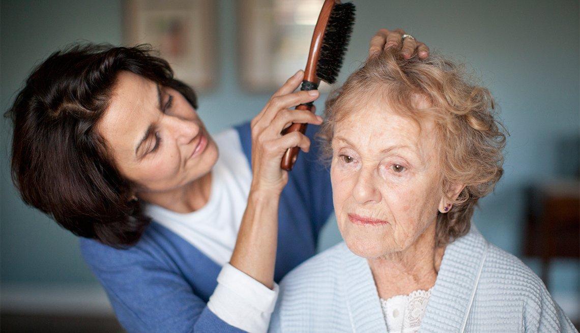 Mujer madura peinando a una mujer mayor