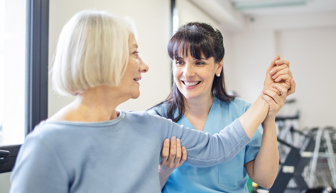 physical therapist moving the arm of a woman patient