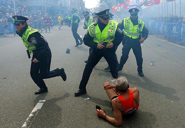 Bill Iffrig lies on the ground as police officers react to a second explosion at the finish line of the Boston Marathon in Boston. (John Tlumacki/The Boston Globe/AP)