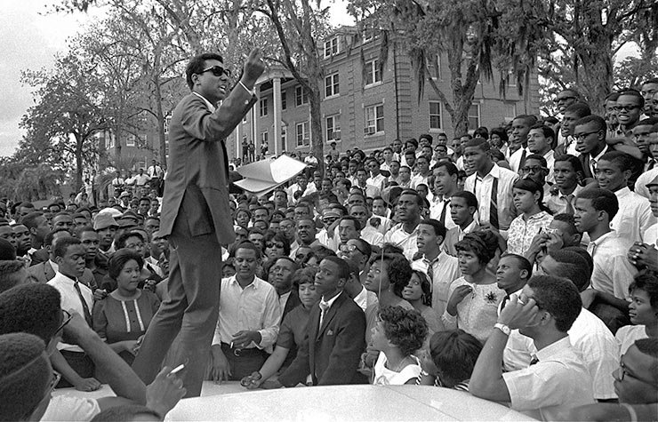 Stokely Carmichael, national head of the Student Nonviolent Coordinating Committee speaks from the hood of an automobile on the campus of Florida A&M University, April 16, 1967, in Tallahassee, Florida, Historical Review of Leading Black Civil Rights Organizations