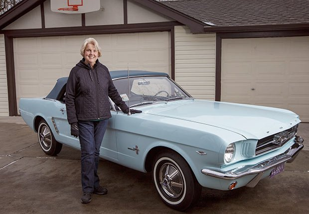 Gail Wise poses with her Skylight Blue 1964 1/2 Ford Mustang convertible outside her garage where it sat for 27 years before its restoration, in Park Ridge, Illinois