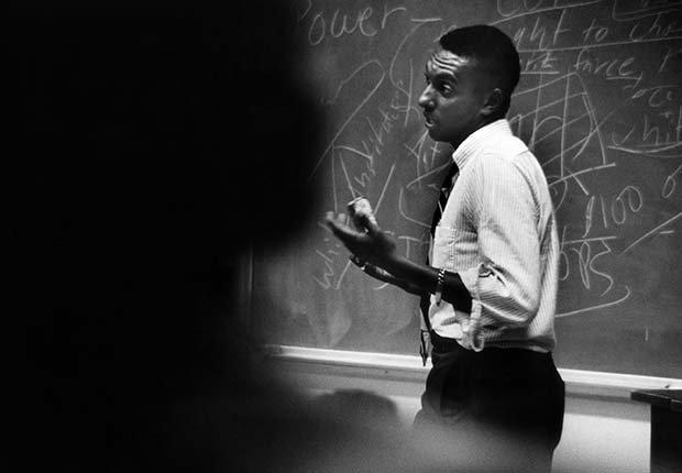 African American man speaking in front of a blackboard