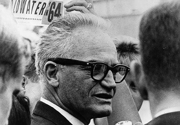 Barry Goldwater standing in a crowd with election signs behind him