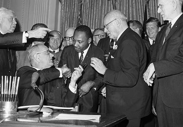 Martin Luther King, Jr. standing next to President Johnson as he signs the Civil Rights Act