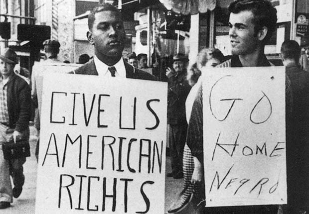 African American man holding sign that reads 'Give us American Rights' with white man holding sign that reads