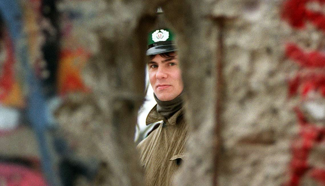 Persona mirando a través de un hueco en el muro de Berlín