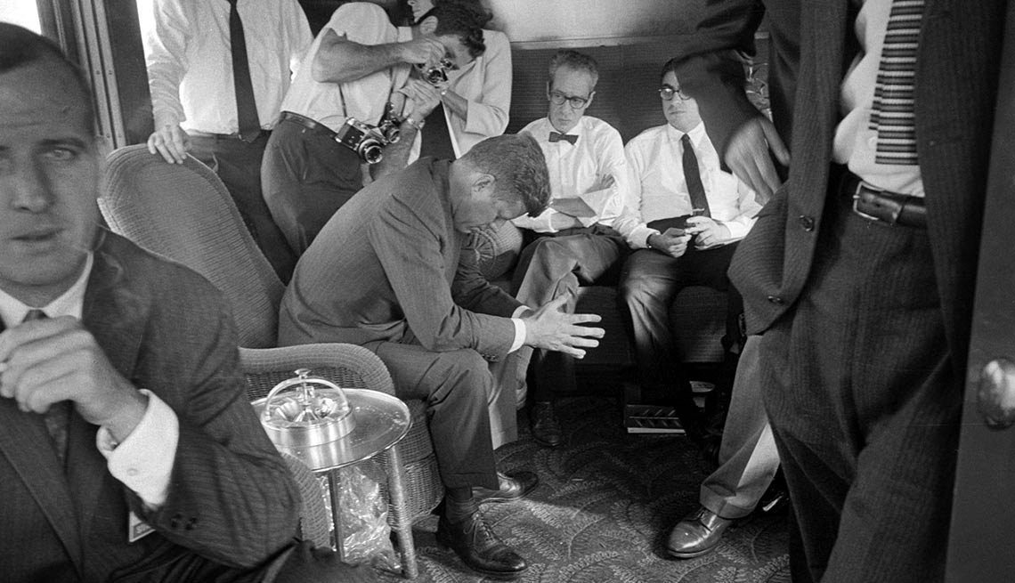 The weary candidate, surrounded by staff and press in a train car, nears the end of a northern California railroad campaign