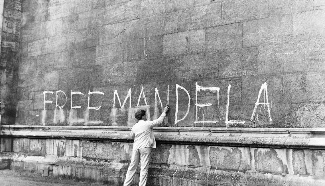 Hombre intenta borrar un escrito en una pared que dice Free Mandela