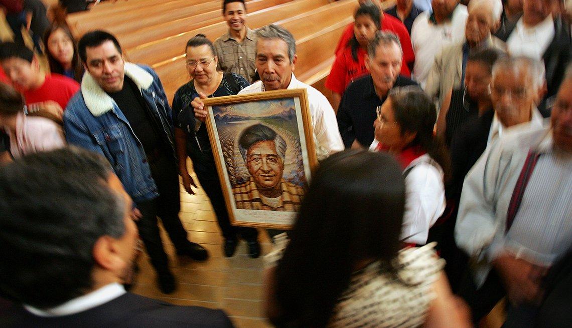 Un hombre sostiene un retrato de César Chávez
