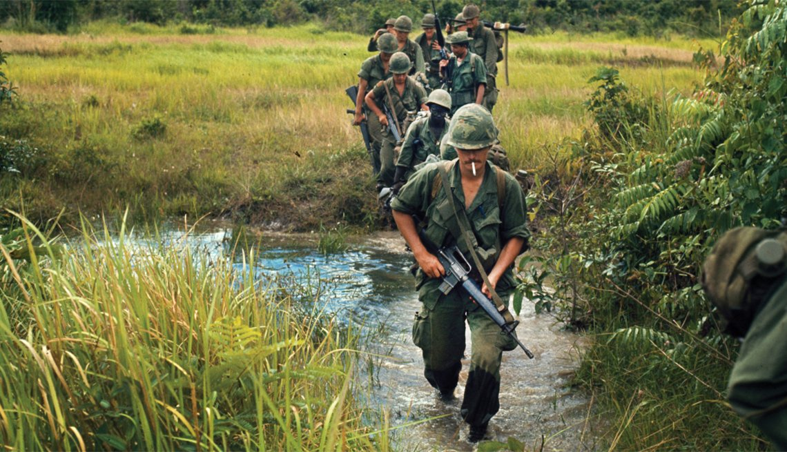 War We Never Saw - Soldiers marching through a rice paddy in Vietnam